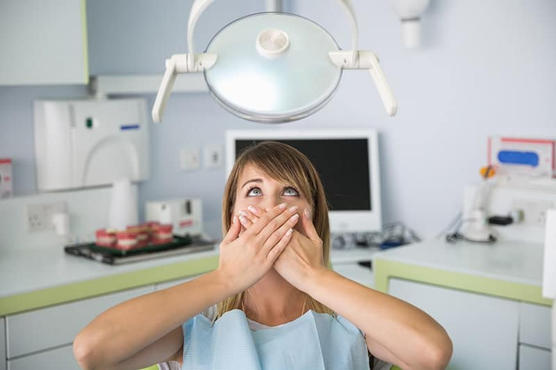 Young woman with dental anxiety covering her mouth will sitting in a dental chair.