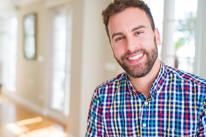Young bearded man in flannel shirt smiles while showing off some imperfections on his smile. Though most worn and chipped teeth aren't very noticeable and don't affect daily life too much, worn teeth can affect your confidence in your smile.