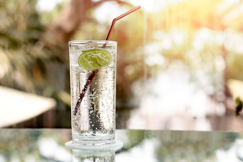 A Hard Seltzer alcoholic beverage sits on a mirrored table outside. Hard seltzer has little to contribute to your oral health.