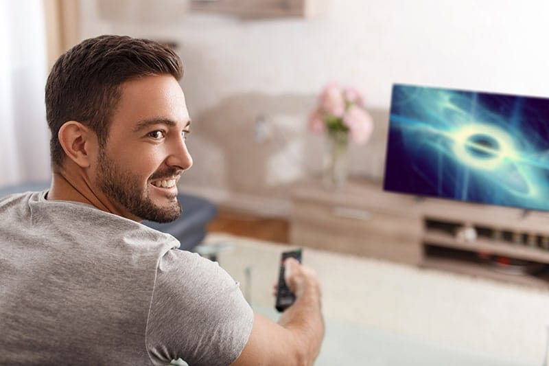 Excited young man ready to watch a show on his high tech television