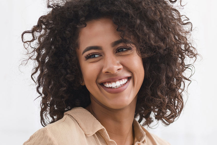 Young woman with curly brown hair shows off her amazing smile