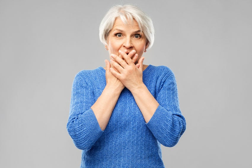 embarrassed older woman covers her mouth