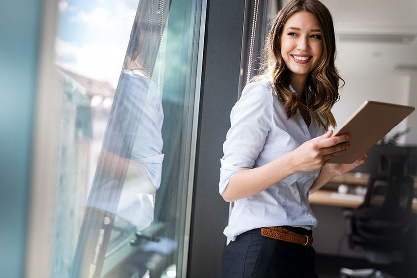 young professional woman leans against her office window