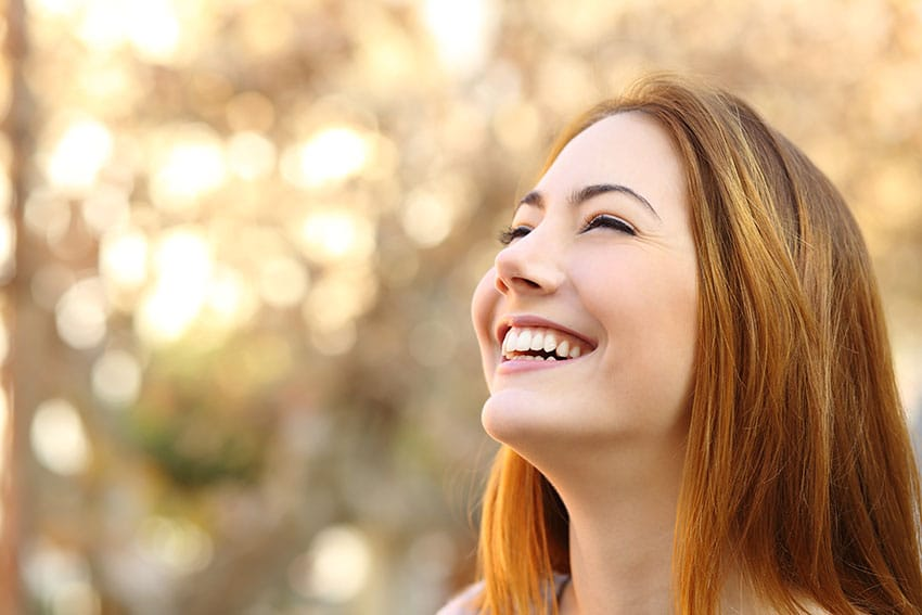 attractive young woman looks up into the beautiful sky
